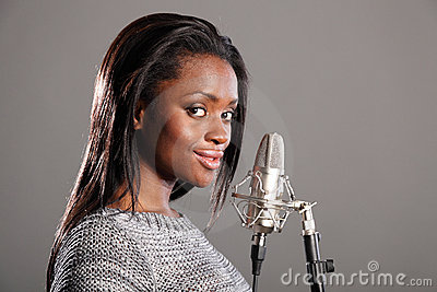 Young black girl making music in recording studio