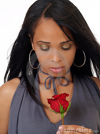 Young black woman looking down at red rose