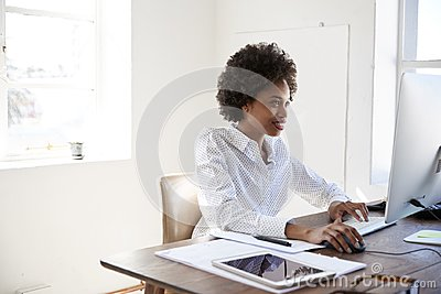 Young black woman working at computer in an office, close up Stock Photo