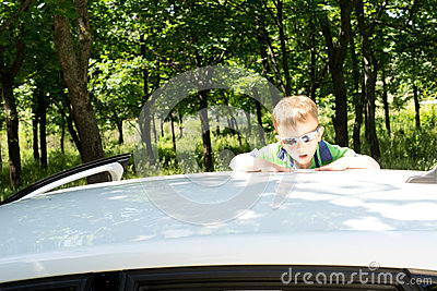 Young blond boy climbing to the rooftop of a car