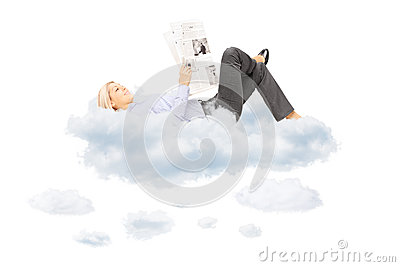 Young blond female reading a newspaper and lying on clouds