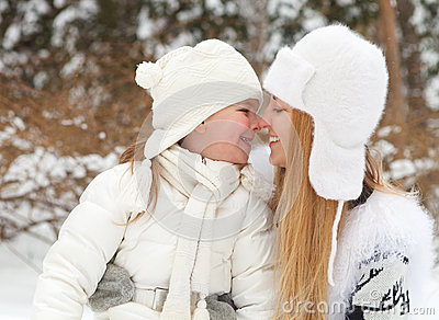 Young blond mother takes care of her daughter outdoors