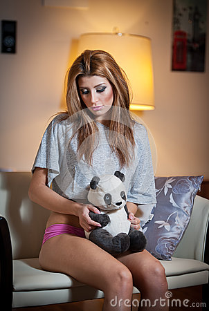 Young blond sensual woman sitting on chair relaxing with a panda bear toy. Beautiful young girl with comfortable clothes relaxing
