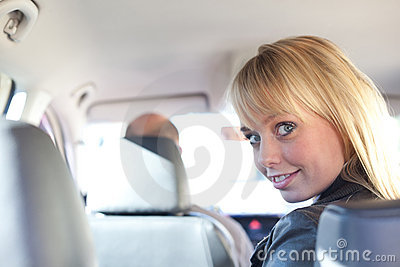 Young blond woman on a backseat of a car