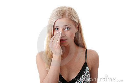 Young blond woman cleaing her face