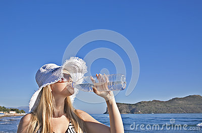 Young blond woman drinks water