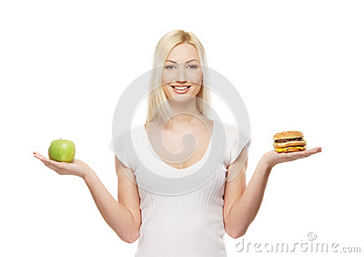 A young blond woman holding a burger and an apple