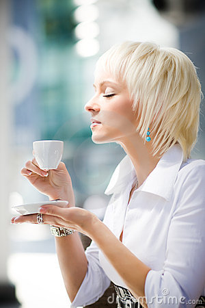 Young blond woman holding cup and tasting coffee