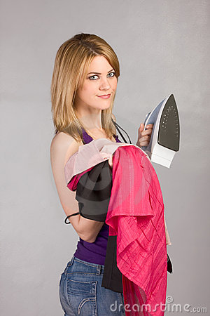 Young blond woman with iron and pile of clothes