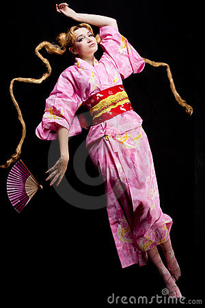 Young blond woman lay in japan kimono on black