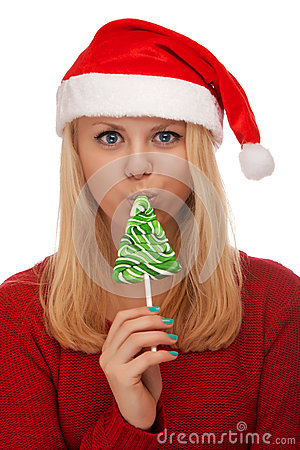 Young blond woman in santa hat with candy