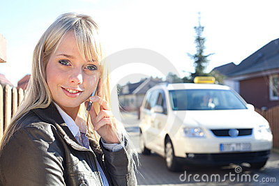 Young blond woman with smartphone and taxicab
