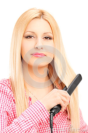 Young blond woman straightening her hair