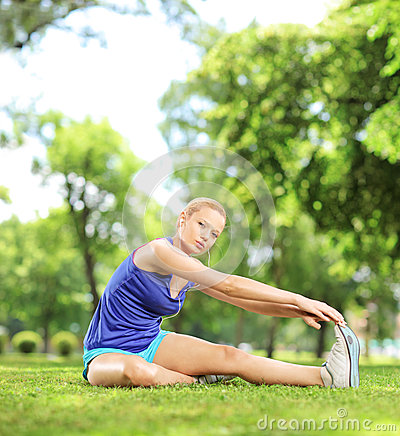 Young blond woman stretching in a park