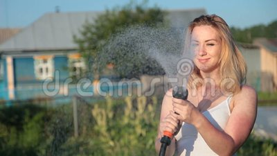 Young blond woman watering a garden. Young woman watering a garden from a hose in sunlight stock footage