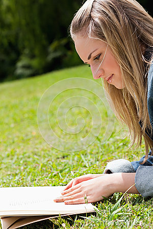 Young blonde girl lying on the grass