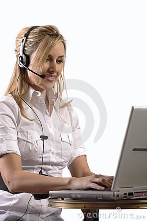 Young blonde girl working on laptop with headset