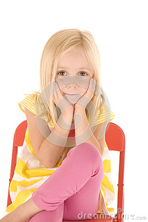 Young blonde girl in yellow striped shirt sitting in red chair c