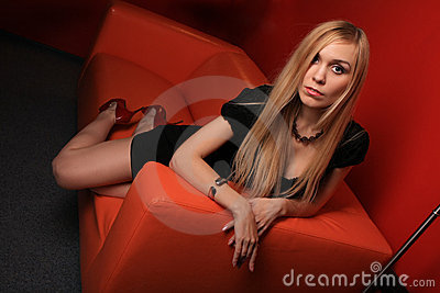 The young blonde on a orange sofa