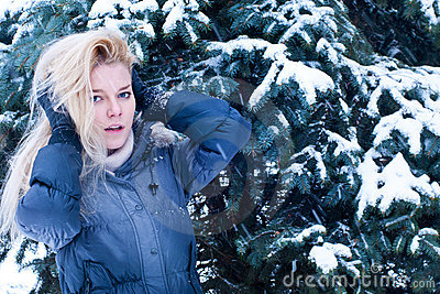 Young blonde standing near the snowed spruce