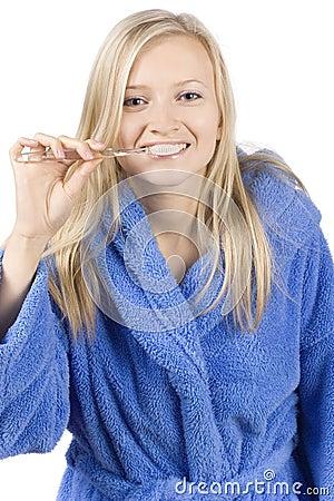 Young blonde woman brushing teeth