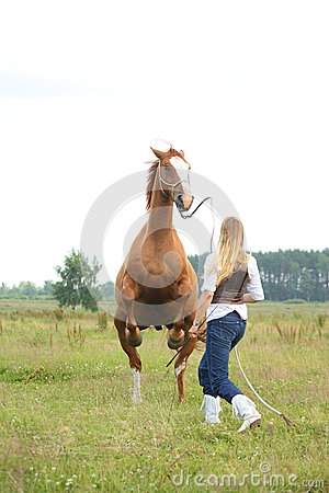 Young blonde woman commanding horse to rear