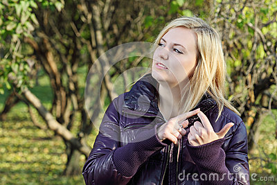 Young blonde woman dreams and counts on his fingers in park