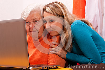 Young blonde woman explains an older an computer