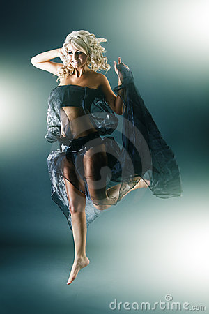 Young blonde woman in funky dress jumping