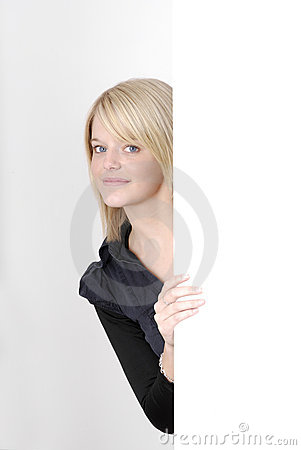 Young blonde woman looking from behind an ad