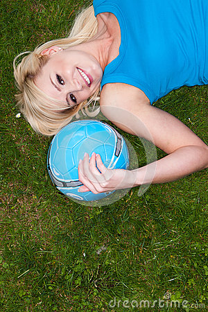 Young blonde woman lying on grass