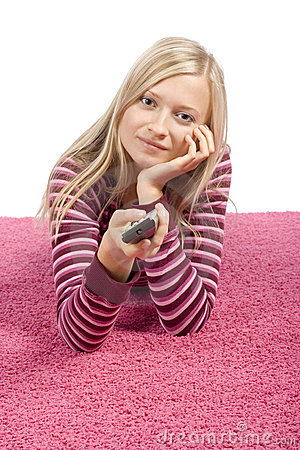 Free Young Blonde Woman Lying On The Pink Carpet With Remote Control Royalty Free Stock Images - 1360589