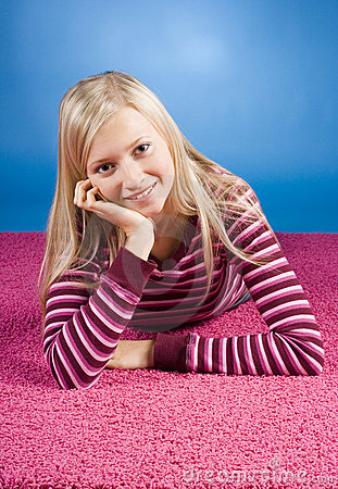 Young blonde woman lying on the pink carpet