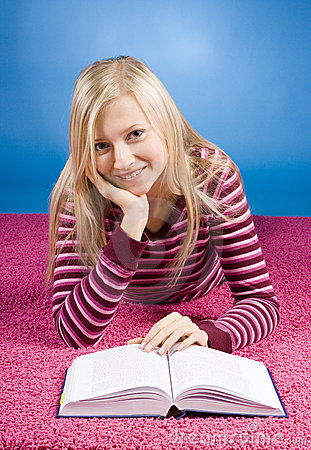 Young blonde woman lying on the pink carpet with book
