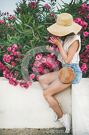 Free Young Blonde Woman Smelling Blooming Oleander Tree Stock Photos - 118769173