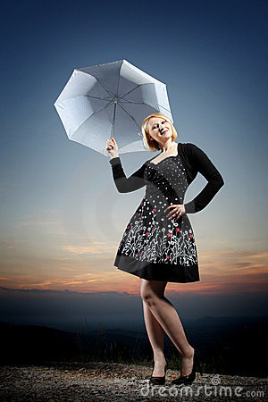 Young blonde woman with umbrella