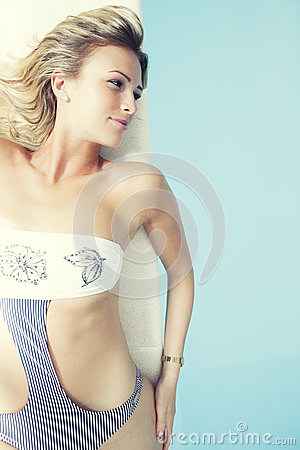 Free Young Blonde Woman With Swimsuit Lying On The Edge Of A Swimming Pool Royalty Free Stock Images - 53765059