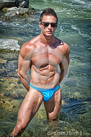 Young bodybuilder standing in river water, shirtless with sunglasses
