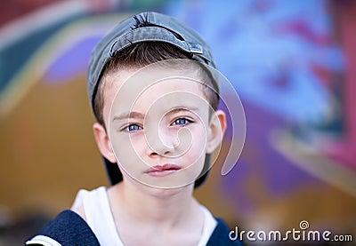 Young boy against graffiti wall