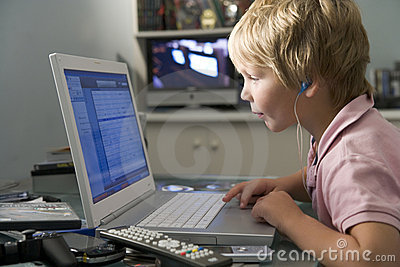 Young boy in bedroom using laptop and listening to