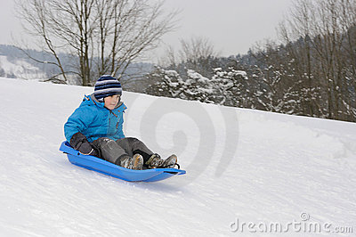 Young boy on blue sled
