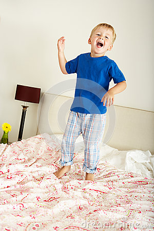 Young Boy Bouncing On Bed