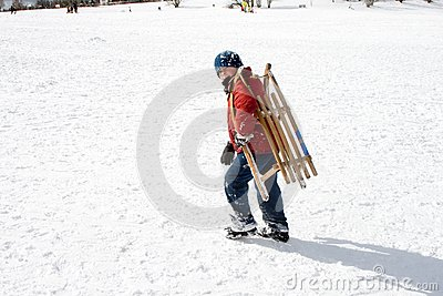 Young boy carries the sledge