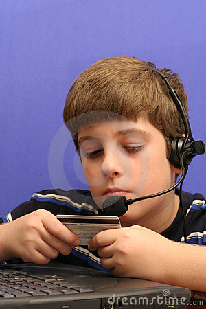 Young boy on computer using credit card blue