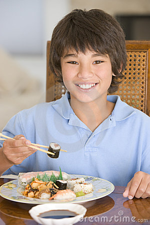 Young boy in dining room eating chinese food
