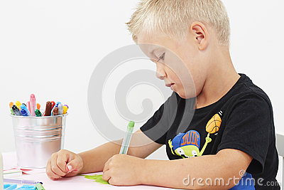 Young boy drawing at table