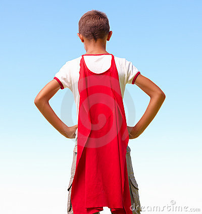 A young boy dressed as superhero, rear view