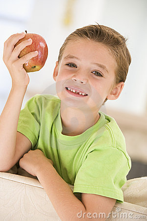 Young boy eating apple in living room