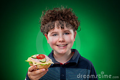 Young boy eating big sandwich