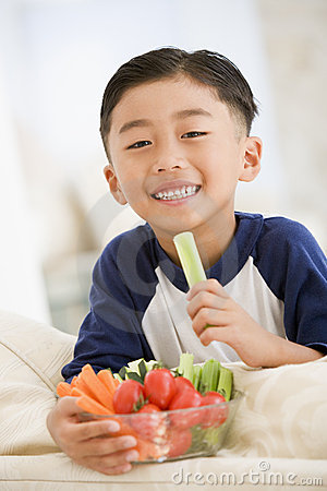 Free Young Boy Eating Bowl Of Vegetables In Living Room Stock Images - 5939044